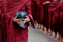 Detail of buddhist monks crowd and person holding a bowl and cup. Detail of buddhist monks crowd in red robes and person holding a bowl and cup Stock Photo