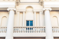 Detail of building with balcony and window. Detail of grand white building in classic style with balcony, square window and two big columns. Arch over window Stock Photos