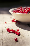 Detail on a bunch of red currant laying on a wooden table with bowl full of redcurrant stock photo