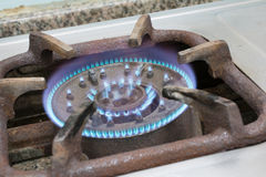 Detail of a burning gas stove with blue flames.  Royalty Free Stock Images