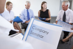 Detail Of Businesspeople Seated In Circle At Company Seminar Stock Photo