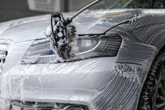 Detail on car front light being washed with soap foam. In car wash Royalty Free Stock Photography