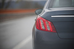 Detail of a car stop light. Detail of the gray car, a red stop light Royalty Free Stock Photos