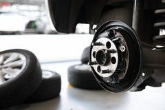 Car suspension & bearing of wheel hub in auto service maintenance. Car lift up by hydraulic, waiting for tire replacement in. Detail of car suspension & bearing stock image