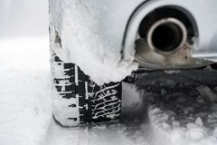 Detail of car tire and exhaust on winter snow.  stock photography