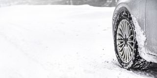 Detail of car winter tire - snow covered road, wide banner, empty space for text left. all logos brands on tyre removed stock photos