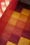 Detail of carpet on the floor with red furniture Stock Photos