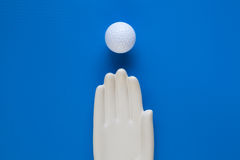 Detail of ceramic hand with golf ball on the blue wooden table Royalty Free Stock Image