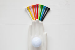 Detail of ceramic hand with golf balls and tees on the white woo. Den desk - Flat Lay Photography Royalty Free Stock Photo