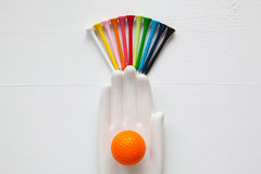 Detail of ceramic hand with golf balls and tees on the white woo. Den desk - Flat Lay Photography Royalty Free Stock Image