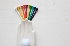 Detail of ceramic hand with golf balls and tees on the white woo. Den desk - Flat Lay Photography Stock Photos