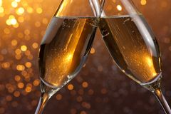 Detail of a champagne flutes with golden bubbles on orange light bokeh background Royalty Free Stock Image