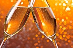 Detail of champagne flutes on orange light bokeh background Stock Photos