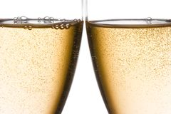 Detail of cheers with two champagne glasses with gold bubbles. On white background Stock Image