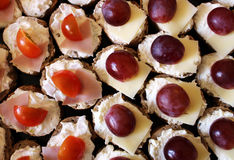 Detail of cheese savory with ham, tomato and grape Royalty Free Stock Photos