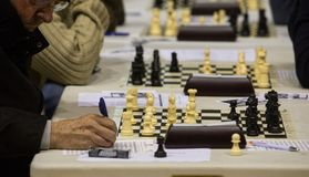 Detail on chess players during gameplay at a local tournament. People play during a local chess tournament in the island of Mallorca.nChess is a two-player Stock Photos