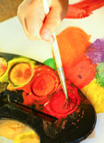 Detail of child's hand painting with watercolor Royalty Free Stock Photo