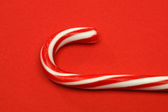 Detail of a christmas candy cane. On a red background Royalty Free Stock Photos
