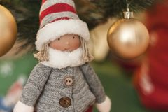 Detail of christmas doll with background of christmas decorations and christmas lights stock photos