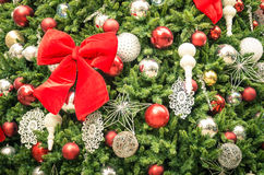 Detail of Christmas tree decorations with red ribbon Royalty Free Stock Photo