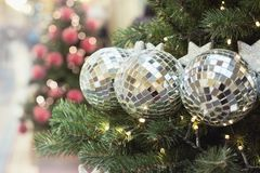 Detail Christmas tree with holiday silver balls and lights with copy space on blurred bokeh background in interiors. Close up. Detail Christmas tree with Royalty Free Stock Photography