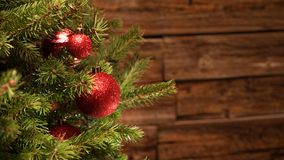Detail of a christmas tree with red glitter balls in front of a wooden wall royalty free stock photography