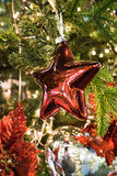 Detail of a christmas tree with a red star. Royalty Free Stock Image