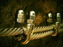 Detail of chrome screws snap hooks and grommets at and of rope. Iron twisted rope fixed together by screws snap hooks. Detail of r Royalty Free Stock Photos