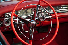Detail of a classic red dream car. Detail of a classic car, red retro car interior, steering vintage wheel, board Stock Images