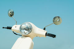 Detail of classic scooter with headlamp and handlebar against sk Stock Photos
