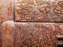 Detail and close up of rust on car metal with cracking, presence of rust and corrosion, beautiful abstract background. Detail and closeup of rust on car metal Royalty Free Stock Photo