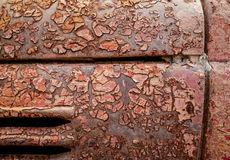 Detail and close up of rust on car metal with cracking, presence of rust and corrosion, beautiful abstract background. Detail and closeup of rust on car metal Royalty Free Stock Images