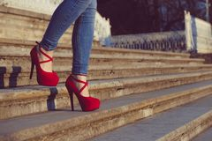 Woman wearing blue jeans and red high heel shoes in old town. The women wear high heels walk on stairs. Sexy legs in red high heel. Detail close up of woman legs Royalty Free Stock Photography