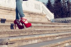 Woman wearing blue jeans and red high heel shoes in old town. The women wear high heels walk on stairs. Sexy legs in red high heel. Detail close up of woman legs Royalty Free Stock Images