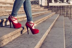 Woman wearing blue jeans and red high heel shoes in old town. The women wear high heels walk on stairs. legs in red high heel stock image