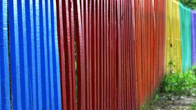 Detail and closeup view of a colorful wooden fence in different colors of the rainbow stock photography