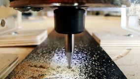 CNC machine cutting wood. A detail of a CNC machine cutting wood for parts Royalty Free Stock Image