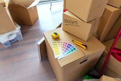 Detail of color palette, metre and cutter. Over moving boxes royalty free stock photo