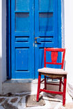 Detail of colorful blue door and red wooden chair Royalty Free Stock Photo