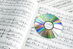 Detail of colorful cd-dvd on piano score Royalty Free Stock Images