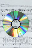 Detail of colorful cd-dvd on piano score Stock Photo