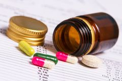 Detail of colorful pills out of container Stock Images