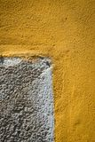 Detail of a colorful wall. A wall very rough draws a gray rectangle over a yellow background in a particular architectural detail Royalty Free Stock Photography