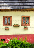 Detail of colorful windows with flowers on old traditional house Royalty Free Stock Photo