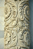Detail of a column at the entrance inside the Baptistery from Piazza dei Miracoli, Pisa, Tuscany, Italy. Details of beautiful stone carvings on a column at the Royalty Free Stock Photos