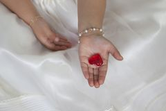 Detail of communion hands of a girl. Dressed in white with a heart in her hand Stock Photography