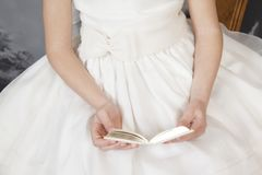 Detail of communion hands of a girl. Dressed in white with a book in her hand Royalty Free Stock Photos