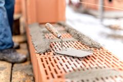 Detail of construction site, trowel or putty knife on top of brick layer Royalty Free Stock Photo