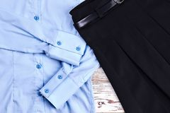 Detail of cotton shirt and pleated skirt. Light blue long sleeve blouse and belted black skirt close up. Girls school apparel Royalty Free Stock Image