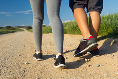 Detail of couple legs walking on the field Royalty Free Stock Images